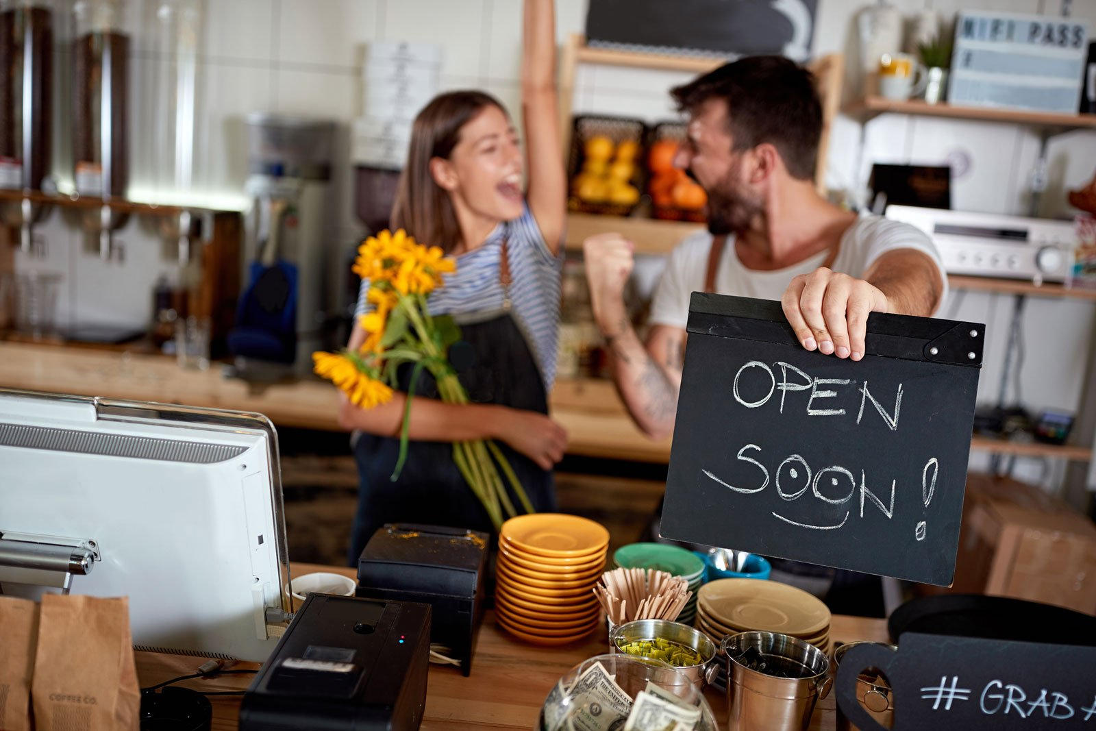 coffee shop owners with open sign