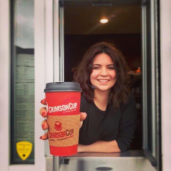 Barista serving specialty coffee drink through drive-thru